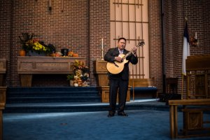 Pastor Eric Song playing his guitar during the groomsmen entrance.